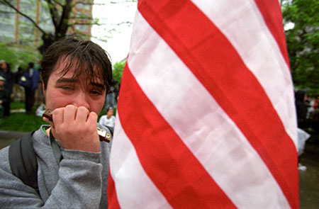 An anti-Globalization protester play harmonica after police used pepper spray on protesters during a meeting of the IMF and the World Bank in Washington, D.C. April 16, 2000